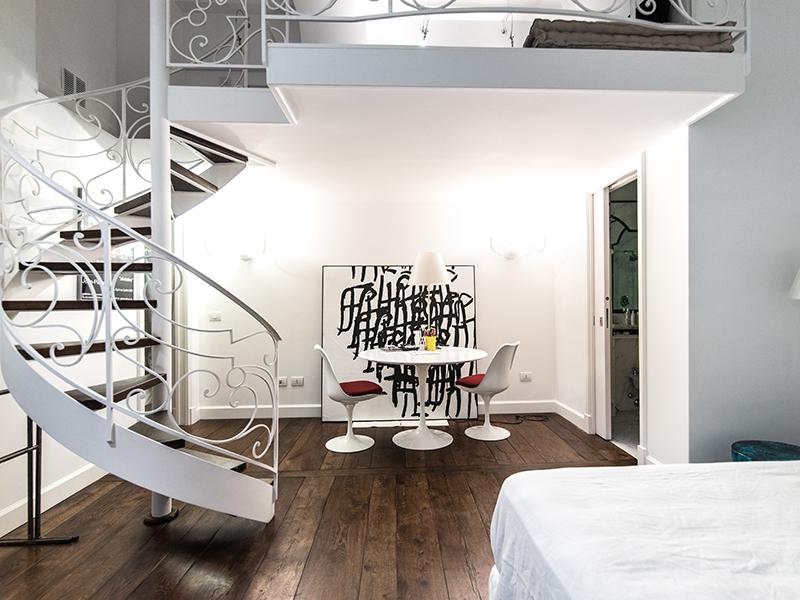 Camera da letto soppalcata con scala a chiocciola artigianale
